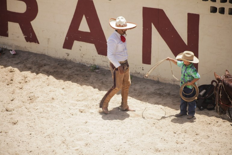 A charro teaches a young boy roping techniques at the 70th anniversary of the Charreada in San Antonio.