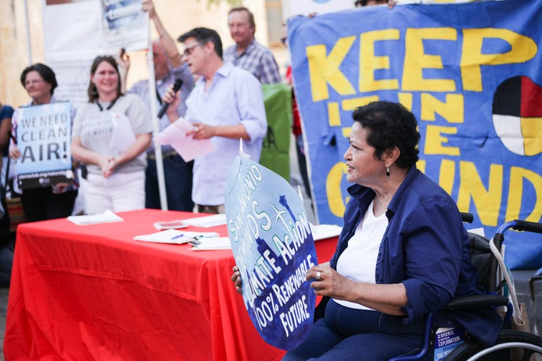 """Supporter Mary Agnes Rodriguez holds up a sign stating """"San Antonio demands climate action 100% renewable future."""""""