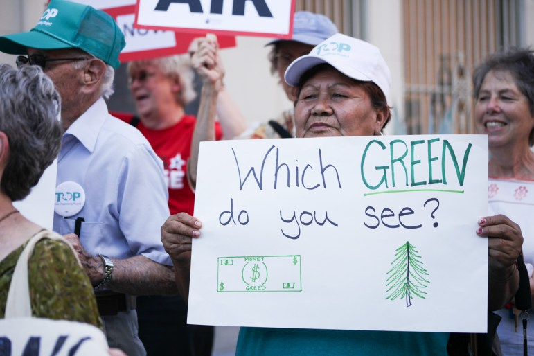 """Supporters hold up signs asking """"Which green do you see?"""" at the rally for the Paris climate accord."""