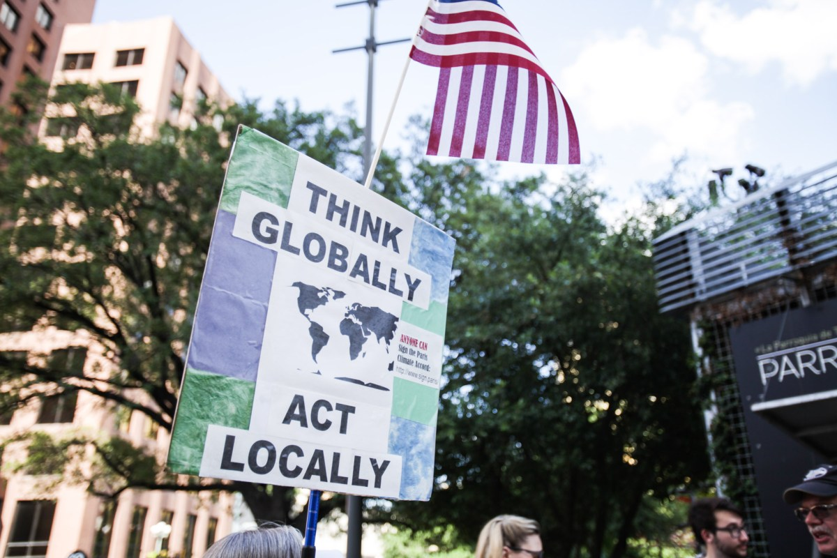 Signs of environmental awareness are held up by supporters in the Municipal plaza.