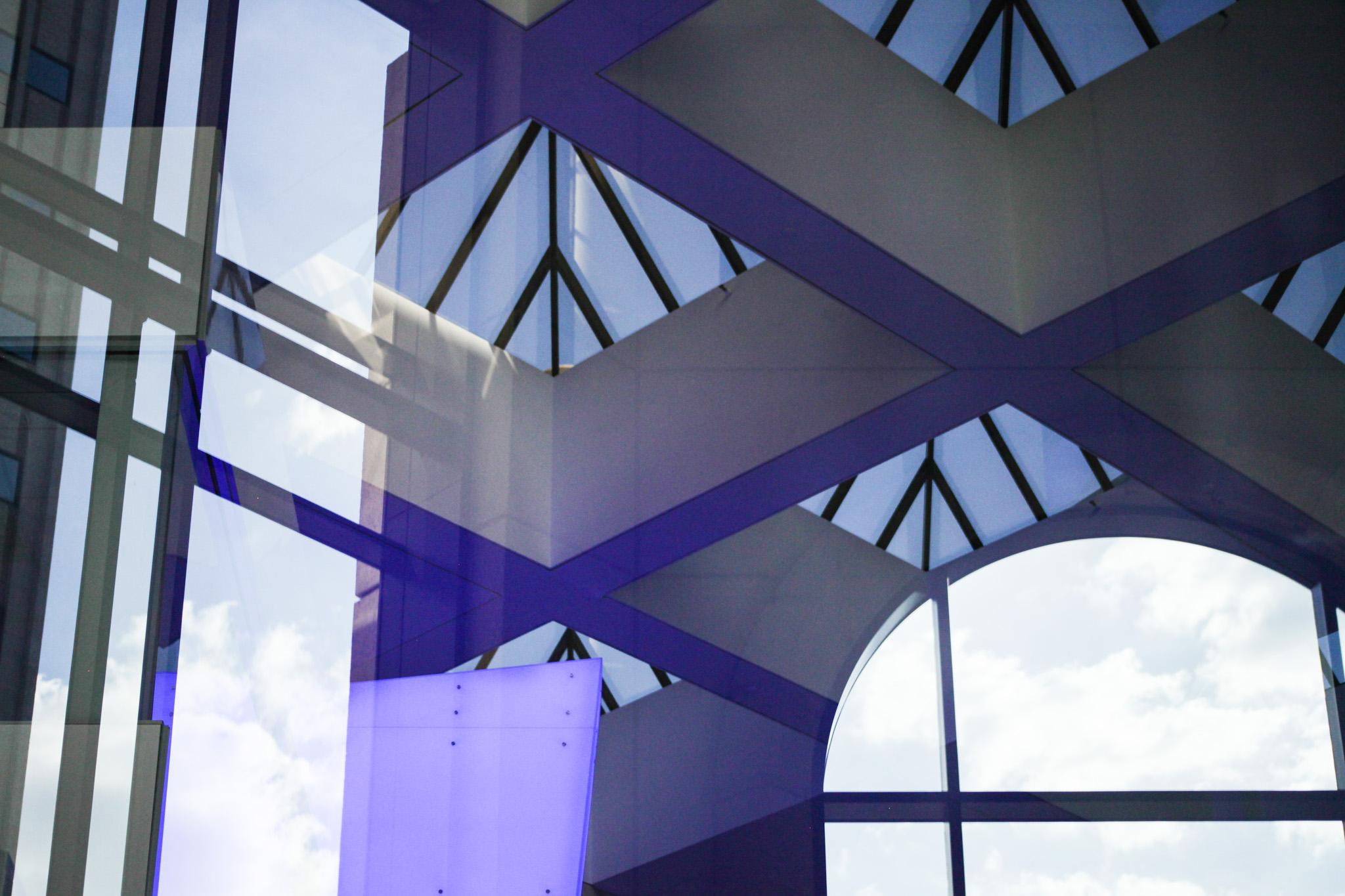 A blue art installation reflects across the windows the BBVA branch.