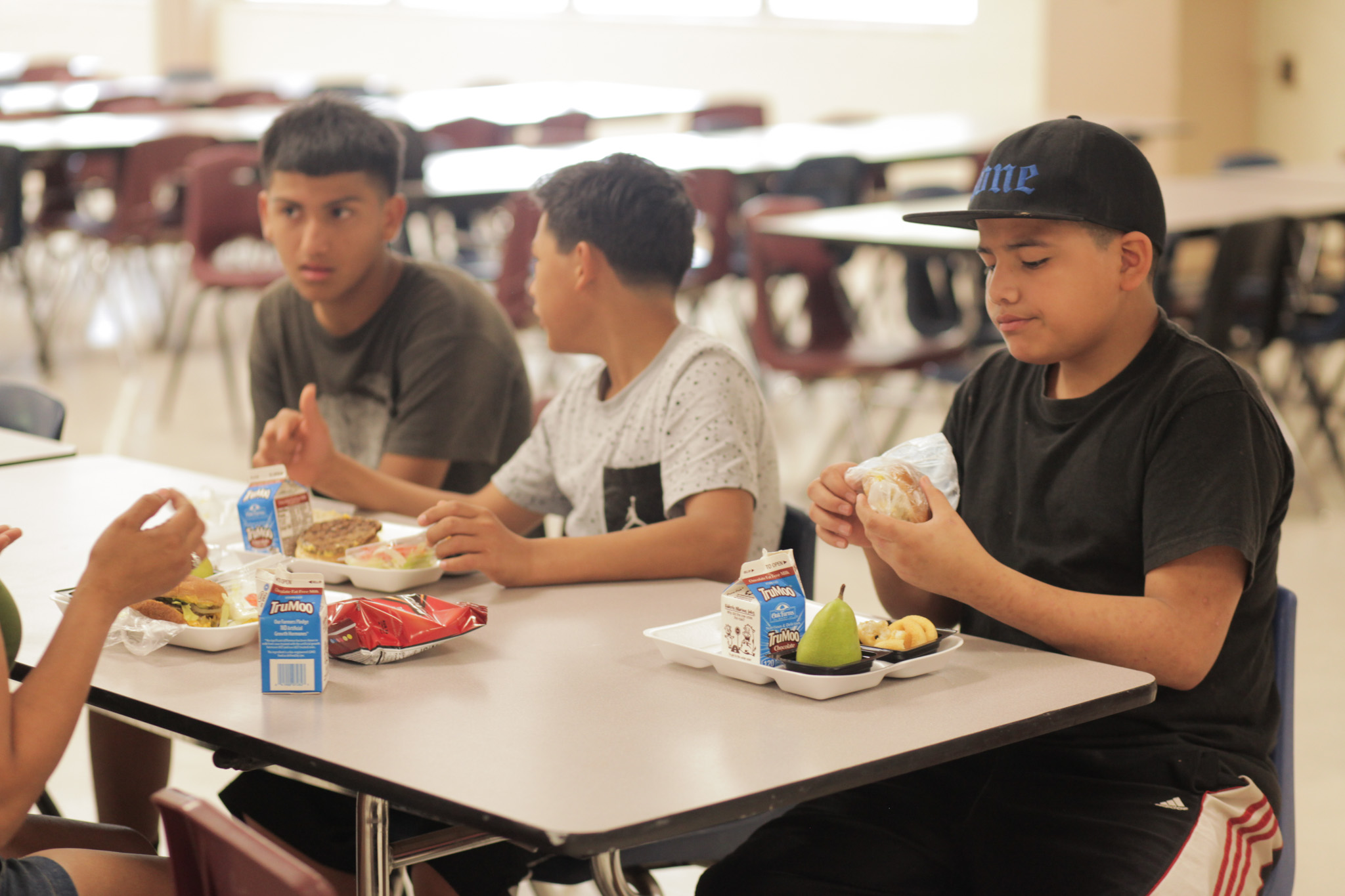 Community members take advantage of the summer food program at Rhodes Middle School.