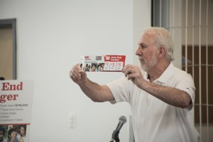 San Antonio Spurs coach Greg Popovich holds up the donation strip from H-E-B which encourages you to add donations to your grocery bill.