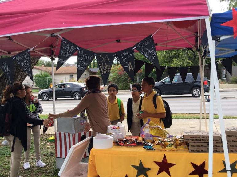 Move SA volunteers hand out snacks to passersby during the nonprofit's voting party on May 6.