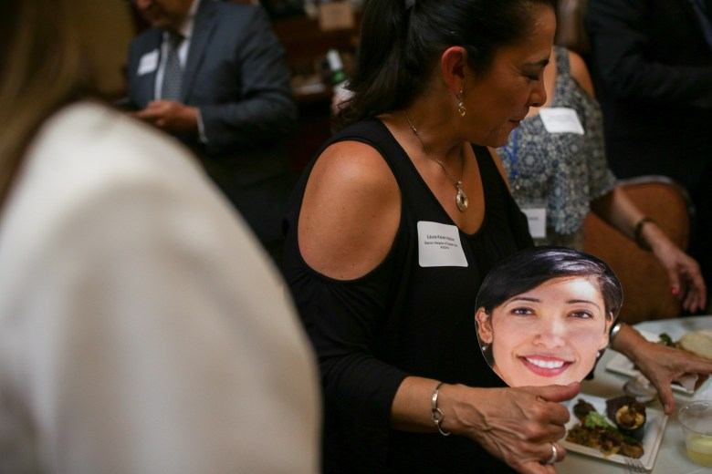 Faces of councilmembers made into fans were given to attendees and filled the space.