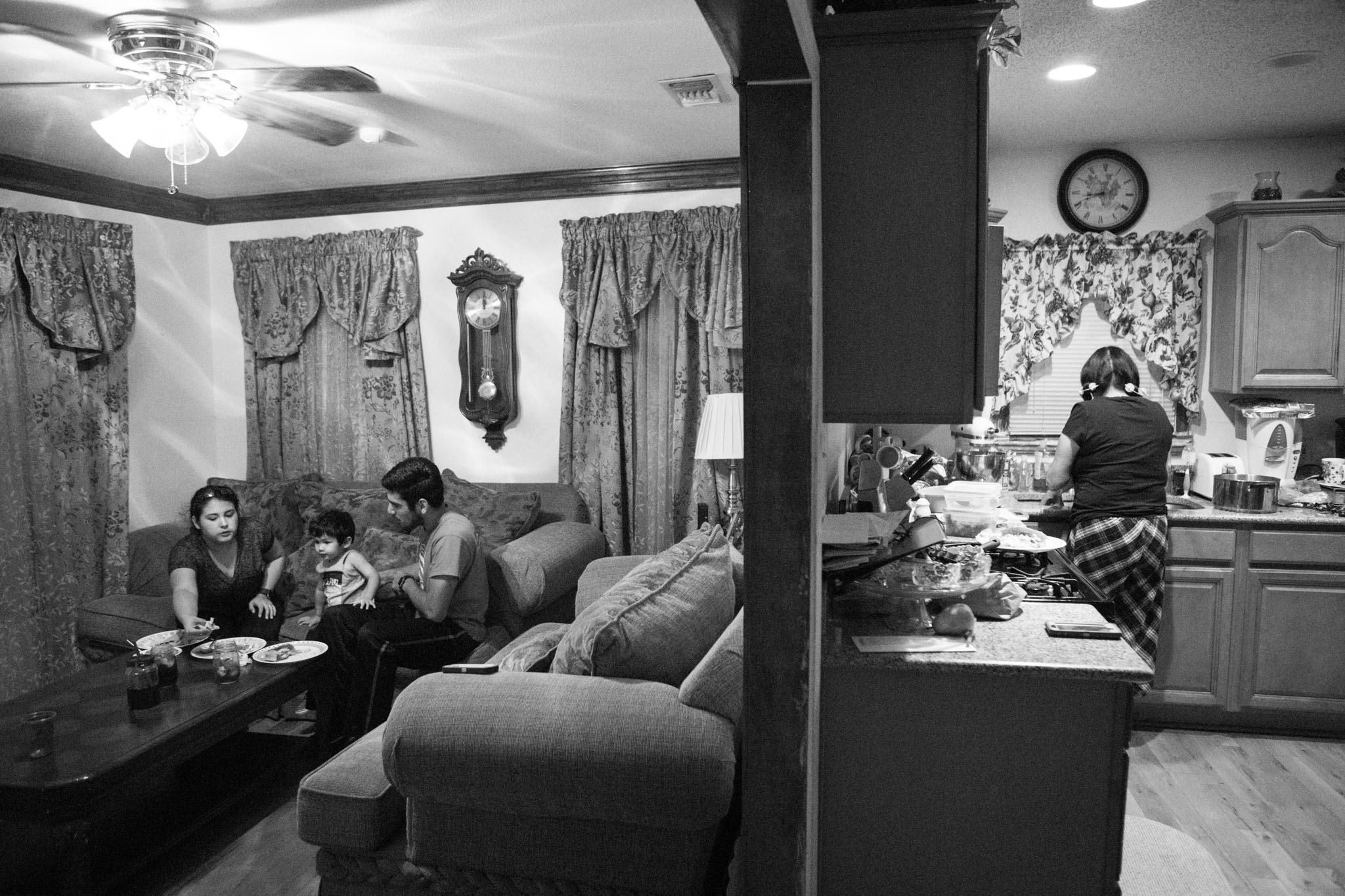(From left) Alaska Martinez, Jimmy, 2, and Jimmy Martinez eat their meal in front of the television as Jimmy's grandmother Mary Gallegos cleans up the kitchen.