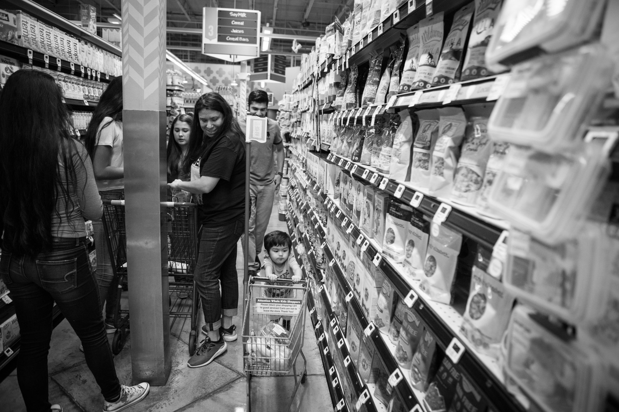 Jimmy, 2, races through the aisles of Whole Foods as his parents, aunts, and grandmother shop for vegan food as part of a healthy lifestyle.