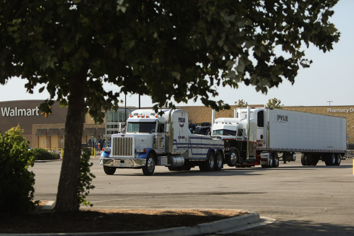 The tractor-trailer is towed out of the Walmart parking lot by a towing truck.