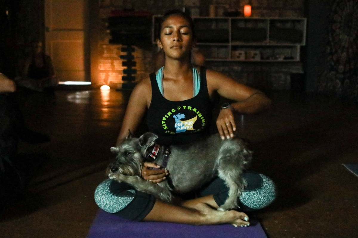 Stephanie Garza rests with her dog in her lap during a session of Dogi at Transcend.