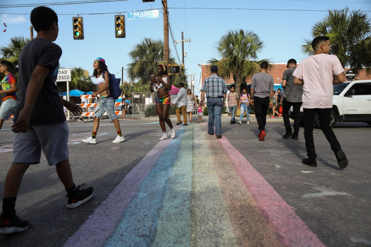 A rainbow crosswalk is drawn in chalk at the corner of Main and Evergreen Streets.