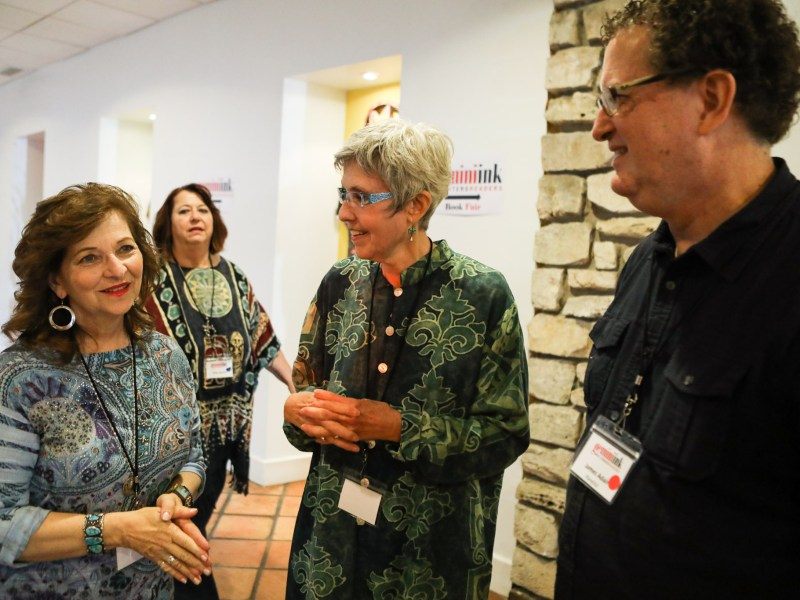 (From left) UTSA Professor of Transformative Children's Literature Carmen Tafolla, Gemini Ink founder Nan Cuba, and Voices de la Luna Editor Jimmy Adair chat in the hallway of El Tropicano Riverwalk Hotel between panels.