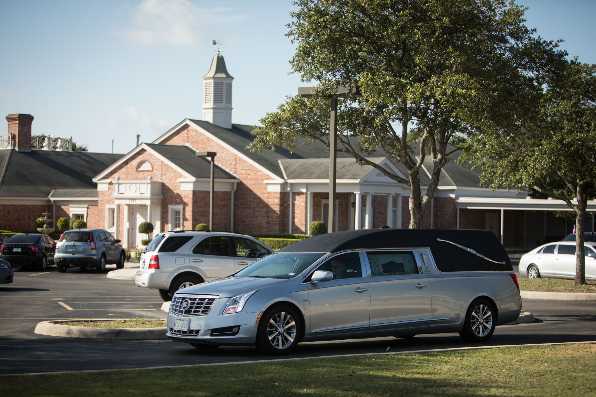 A hearse with deceased Jaime Martinez leaves in a funeral procession from Porter Loring Mortuary North.