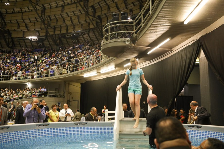 A girl steps down into the pool where she is baptized during the 2017 convention of Jehovah's Witnesses in the Freeman Coliseum.