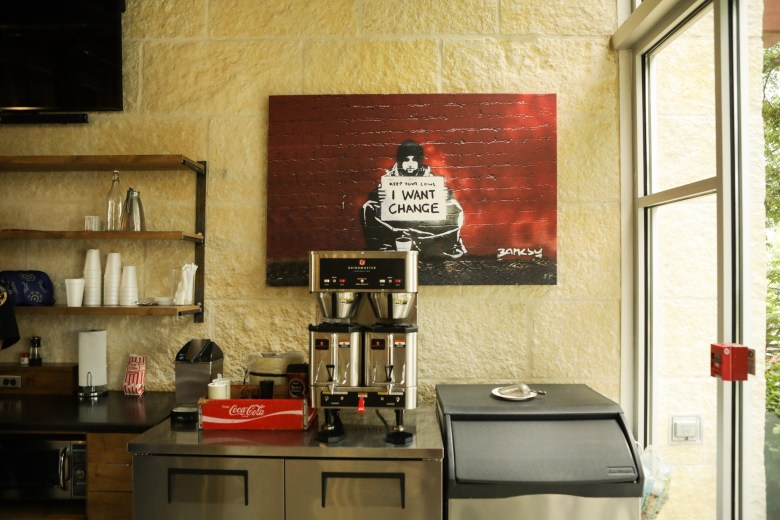 Artwork possibly by Banksy is placed above the coffee machine in the lobby at The Phipps.