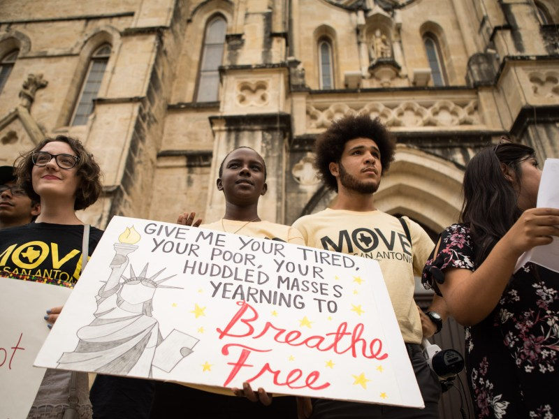 (From left) Chiara Pride, Jolie Nyamarembo, Sean Rivera, and Arlenne Serna hold up signs at the vigil for migrant deaths at San Fernando Cathedral.
