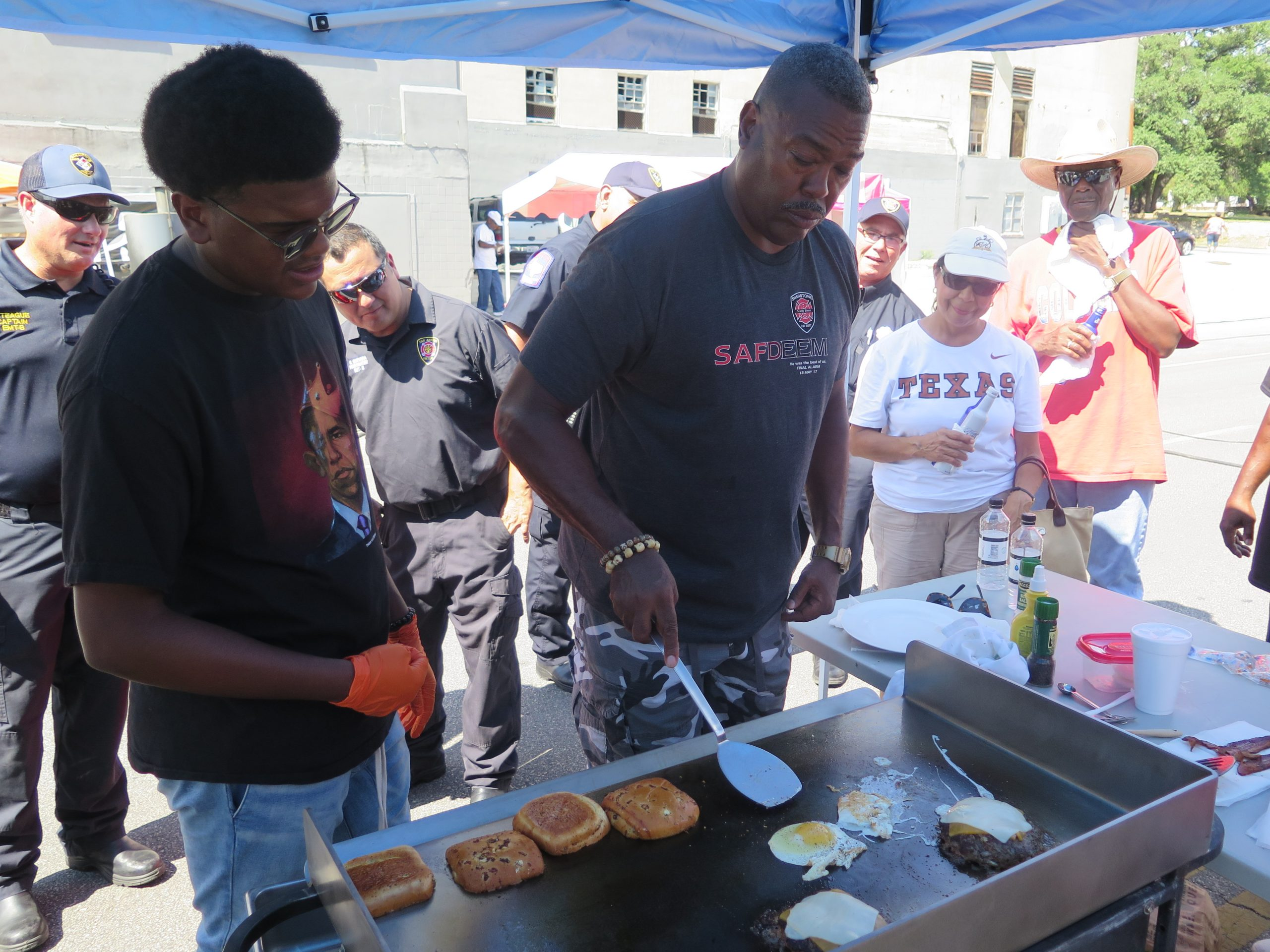 Attendees watch as San Antonio Fire Department Chief Charles Hood fries eggs during the burger cook-off at the third All-American Burger Festival.