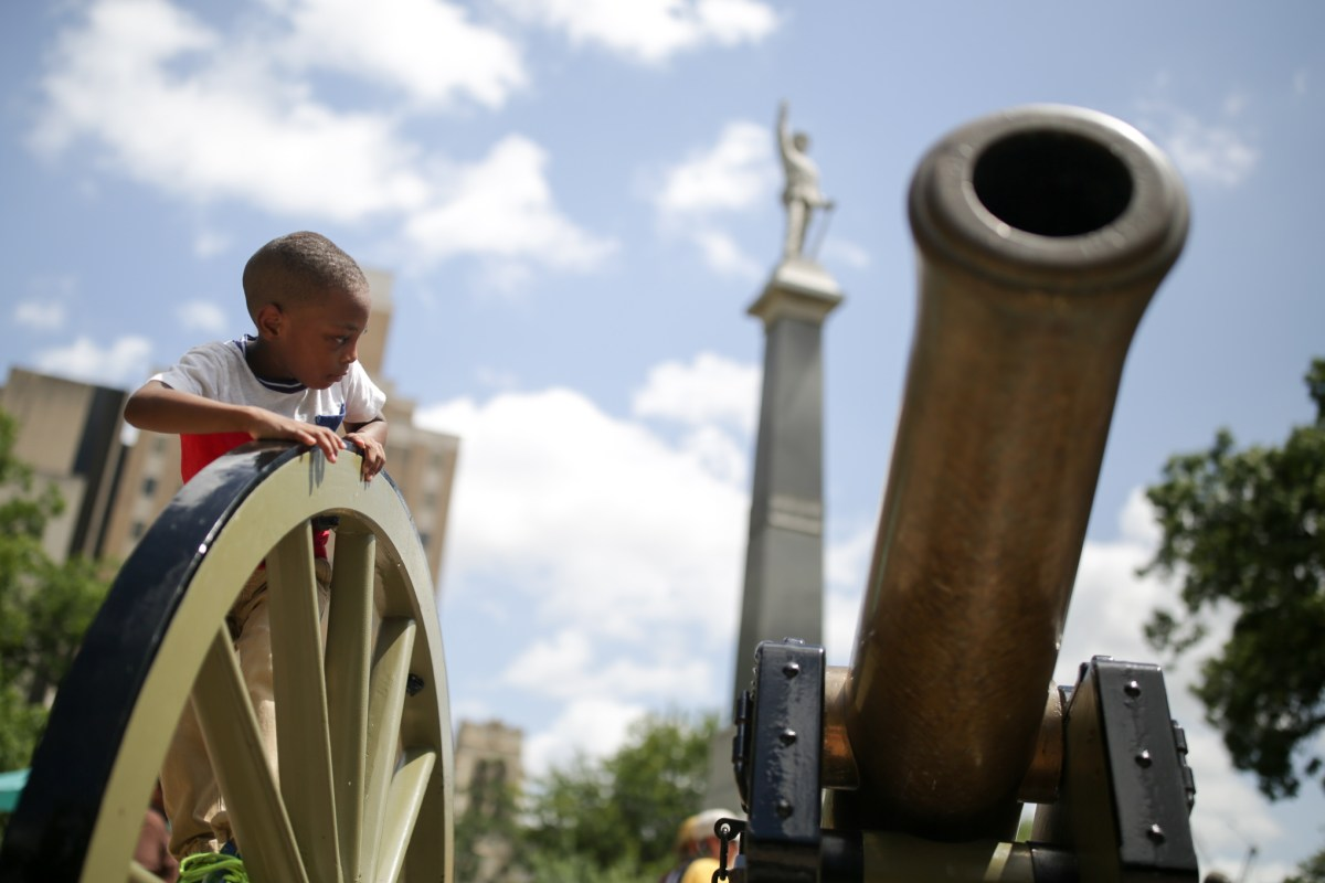 Joshua, 4, climbs on top of a historic canon at Travis Park during the protest.