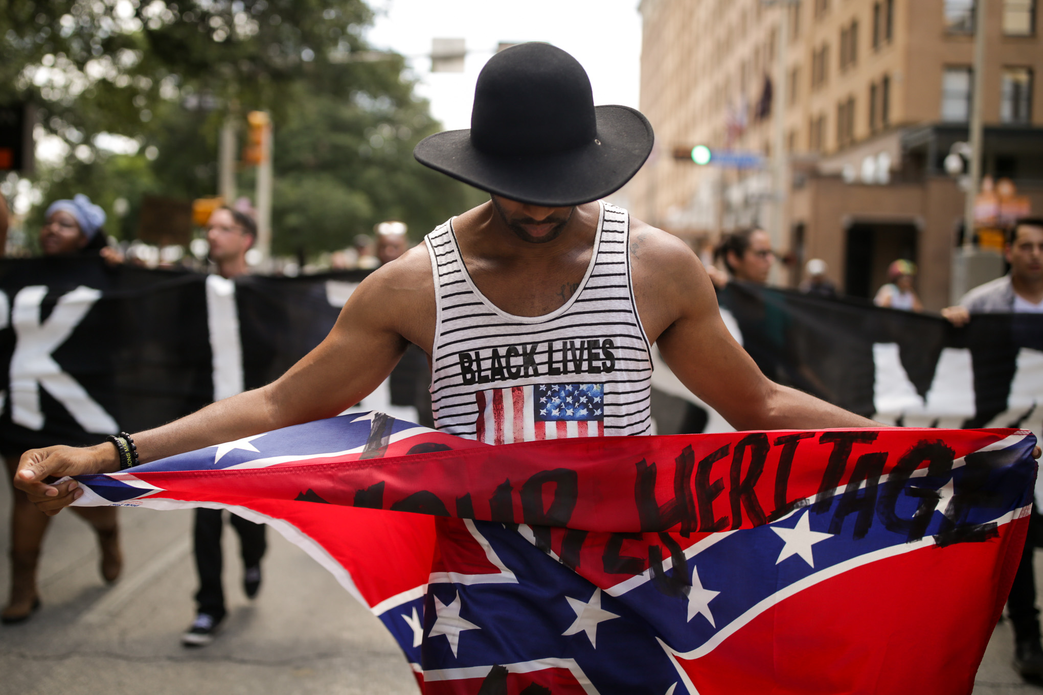 Mike Lowe walks with a defaced Confederate flag following a rally against the Confederate monument at Travis Park.