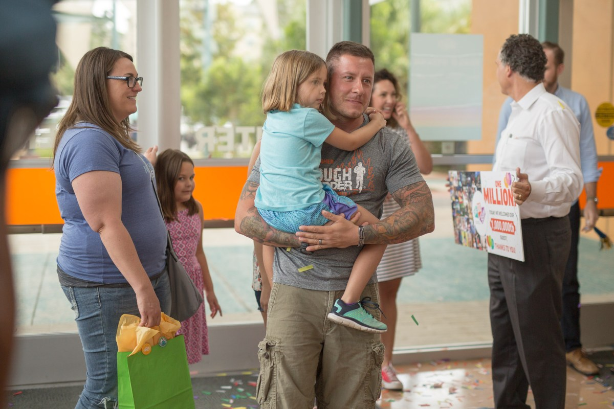 Garrett Rogers with his daughter Ellie, 5, walk in as they are announced as the one millionth visitor to the DoSeum.