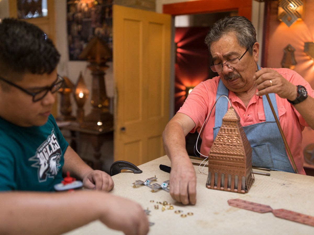 Gregorio Rebollar and his grandson Abel Gonzales finish adding hardware to a piece.