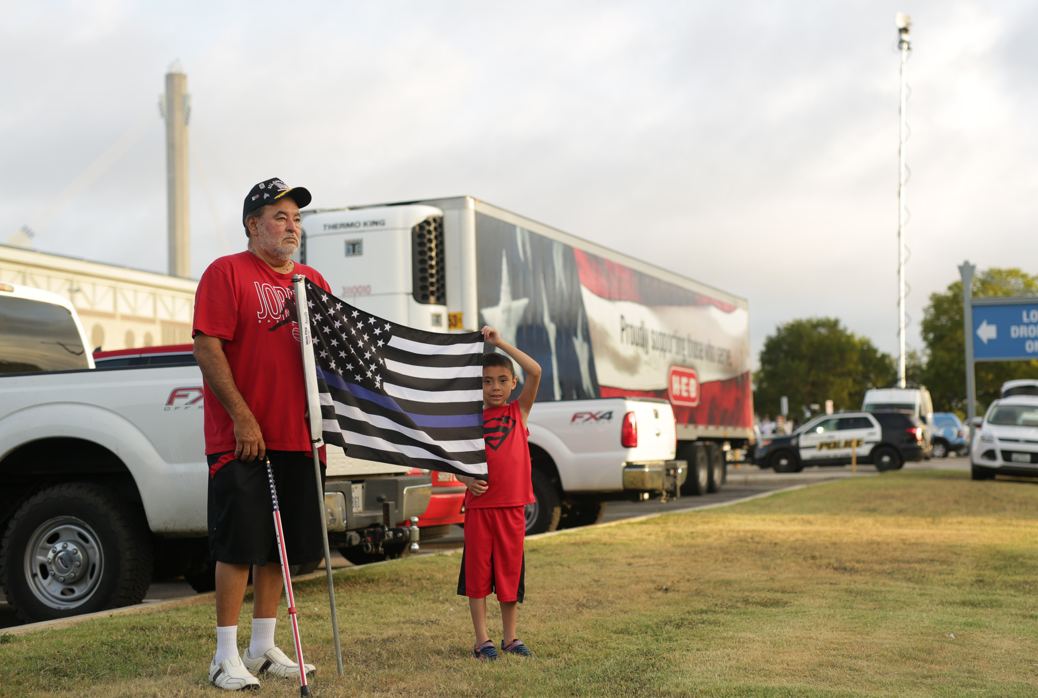 Ruben Gutierrez and Matthew, 7, hold a thin blue line flag at the procession.