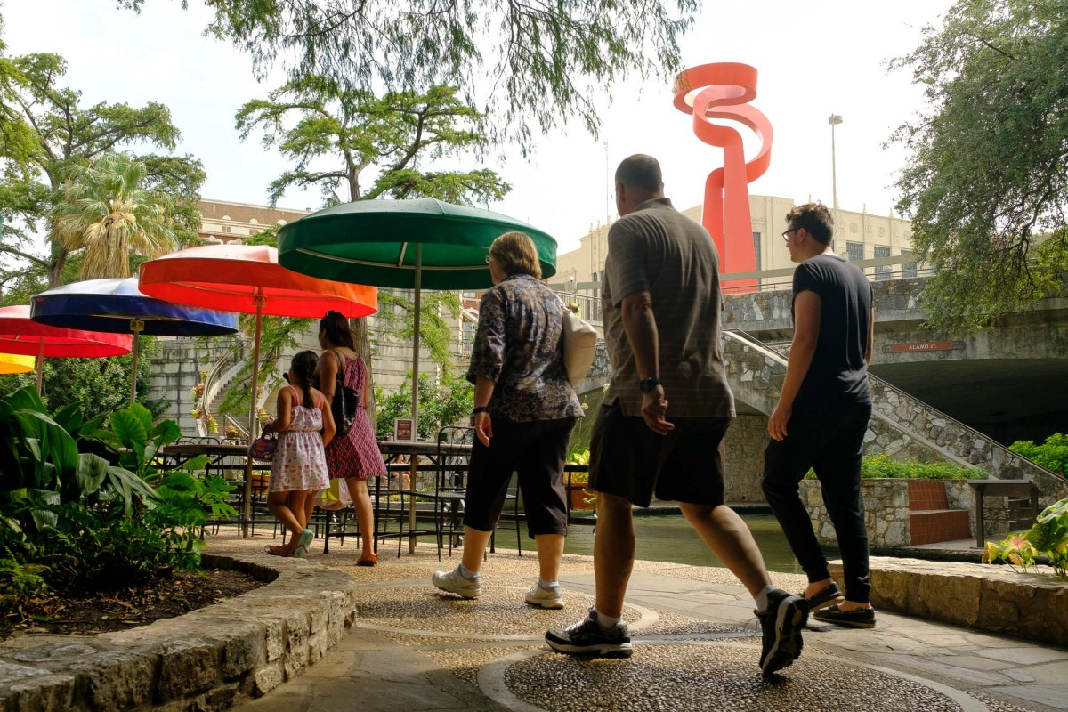 Tourists walk along the San Antonio Riverwalk near Alamo Street.