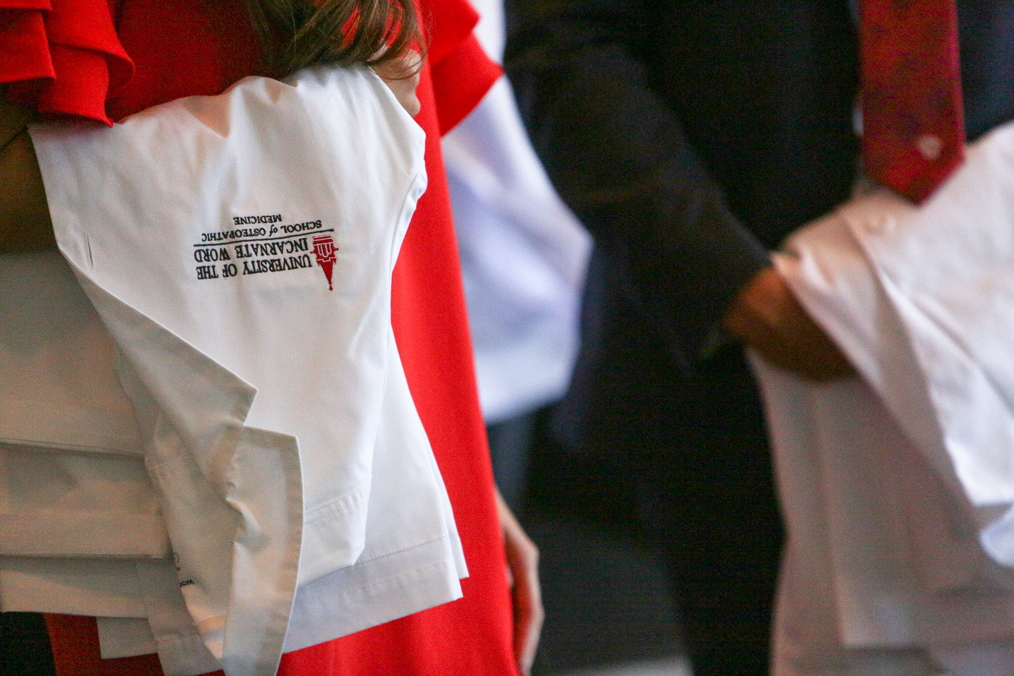 A white coat is draped across a students arm as she arrives to the ceremony.