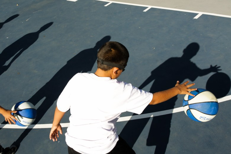 Children practice stationary dribbling during the Westside Pride summer basketball camp.