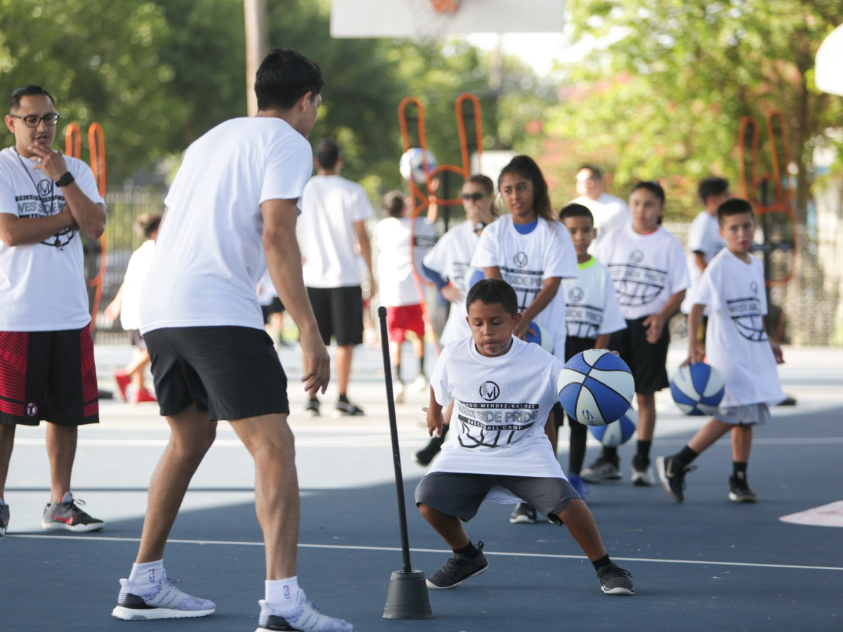 Children are broken into groups of 8 as they work on different basketball techniques.