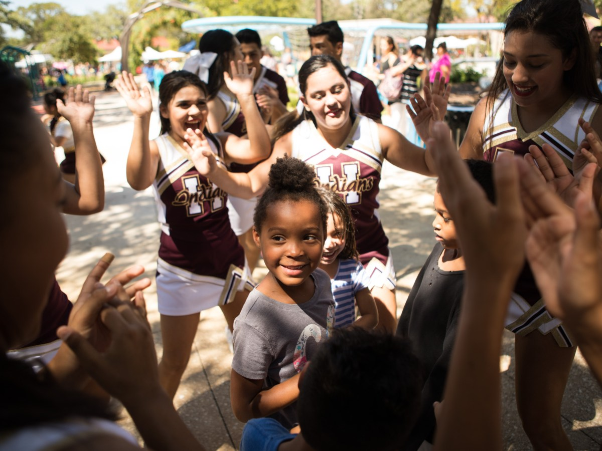 Anyda dances in the middle of a circle of Harlandale High School cheerleaders at the Back to School Bash in Hemisfair Park.