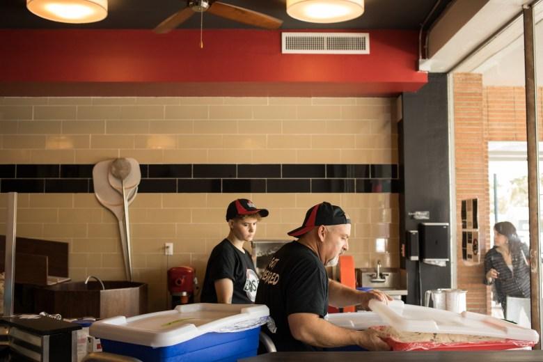 (From left) Boss Bagel Baker Savannah Ballard assists Boss Bagel Co-Owner Brannon Soileau in the making of bagels as a customer peeks in the front window of Boss Bagel.