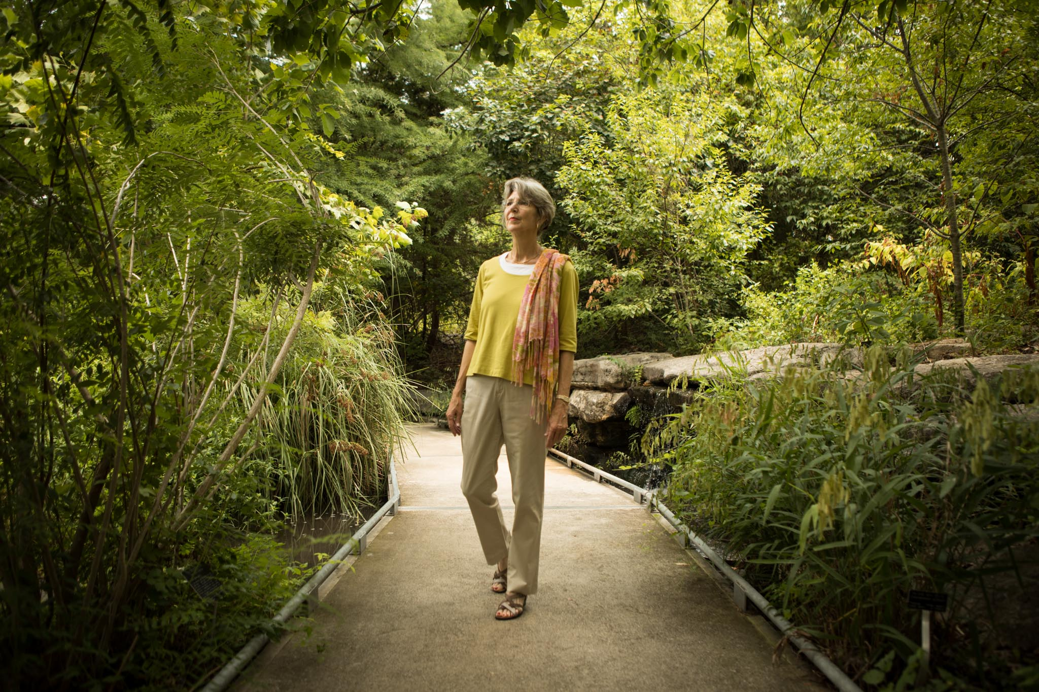 San Antonio Botanical Garden Society, Inc. Former Director of Community Relations and Visitor Services Candace Andrews walks through Hill Country Seep in the San Antonio Botanical Garden.