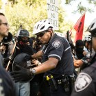 Police officers push back rowdy demonstrators in support of the removal of the Confederate monument in Travis Park.