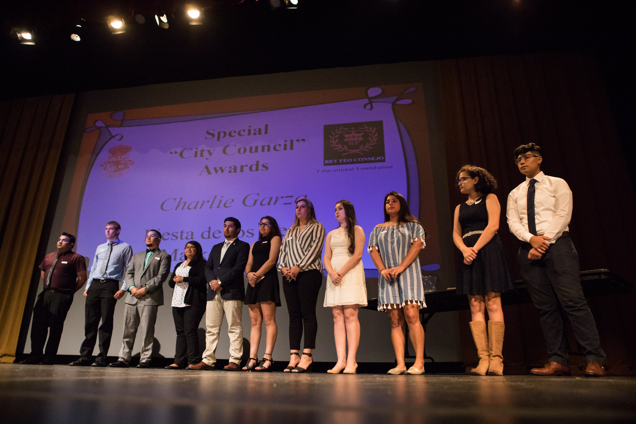"""Scholarship recipients representing the Special """"City Council"""" Awards stand on stage at the Rey Feo Scholarship Awards Ceremony."""