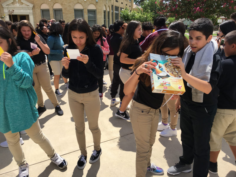 Students at Harris Middle School use a variety of viewing techniques to catch the beginning of the solar eclipse.