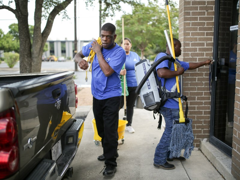 (from left) Brian Wilson, Bridgett Pineda, and David O'Neal carry equipment into a business that they clean five days a week.