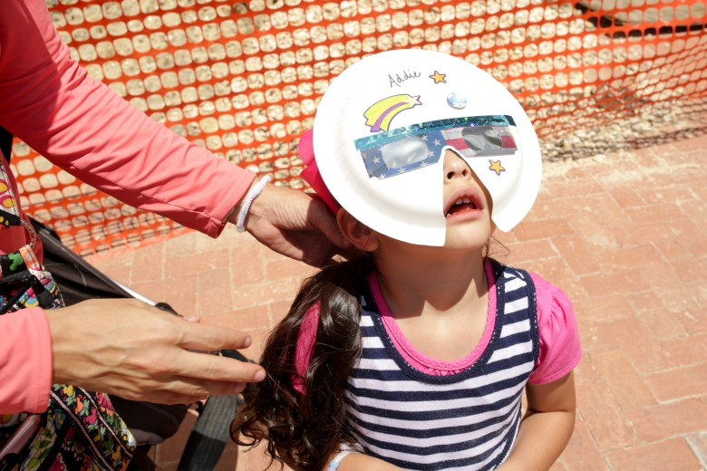 Addie, 4, stares at the partially eclipsed sun through a homemade mask.