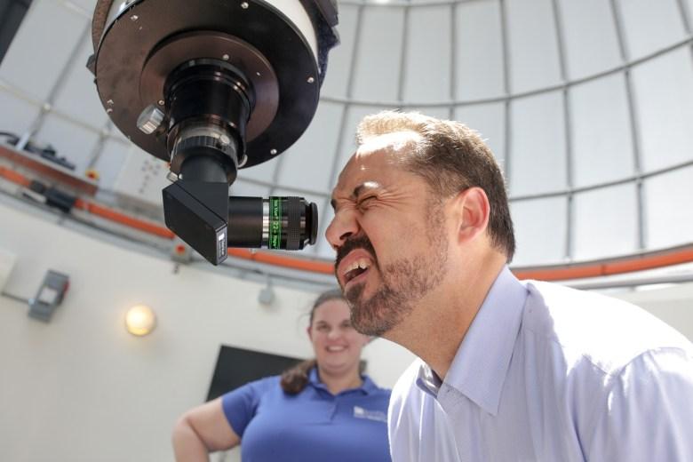 Texas State Senator Jose Menendez looks through a telescope at the Cheever Star Tower at the Scobee Planetarium.