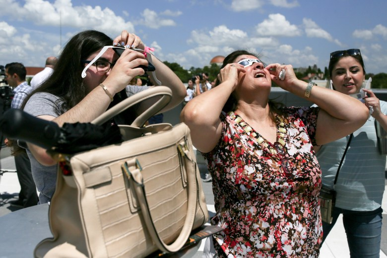 Lindsey and Rosa Holguin use different methods on viewing the solar eclipse.