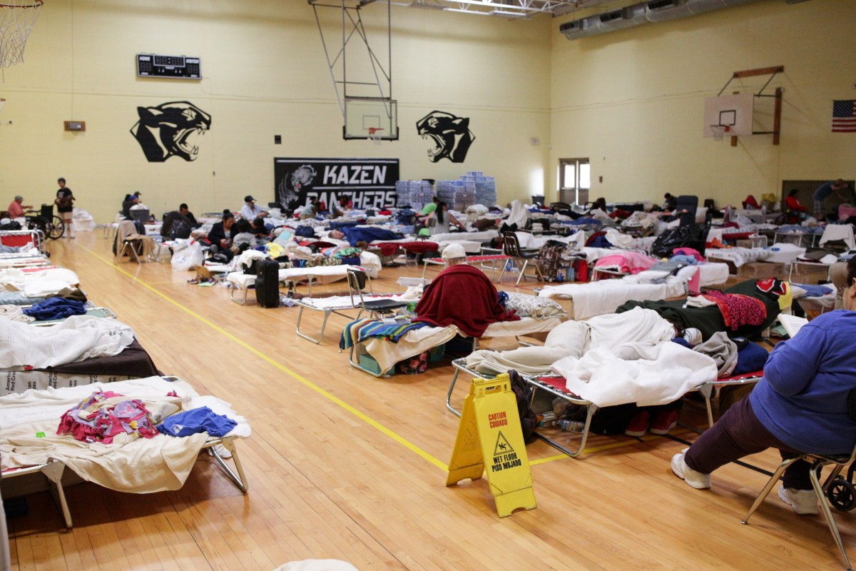 Cots for displaced evacuees line the gymnasium floor at Kazen Middle School in San Antonio.