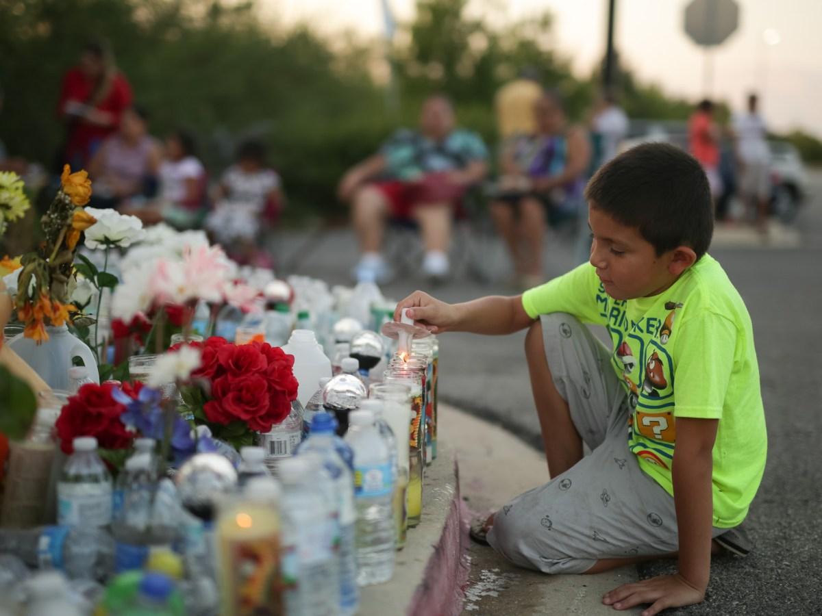 Orlando, 9, lights candles placed at the vigil.