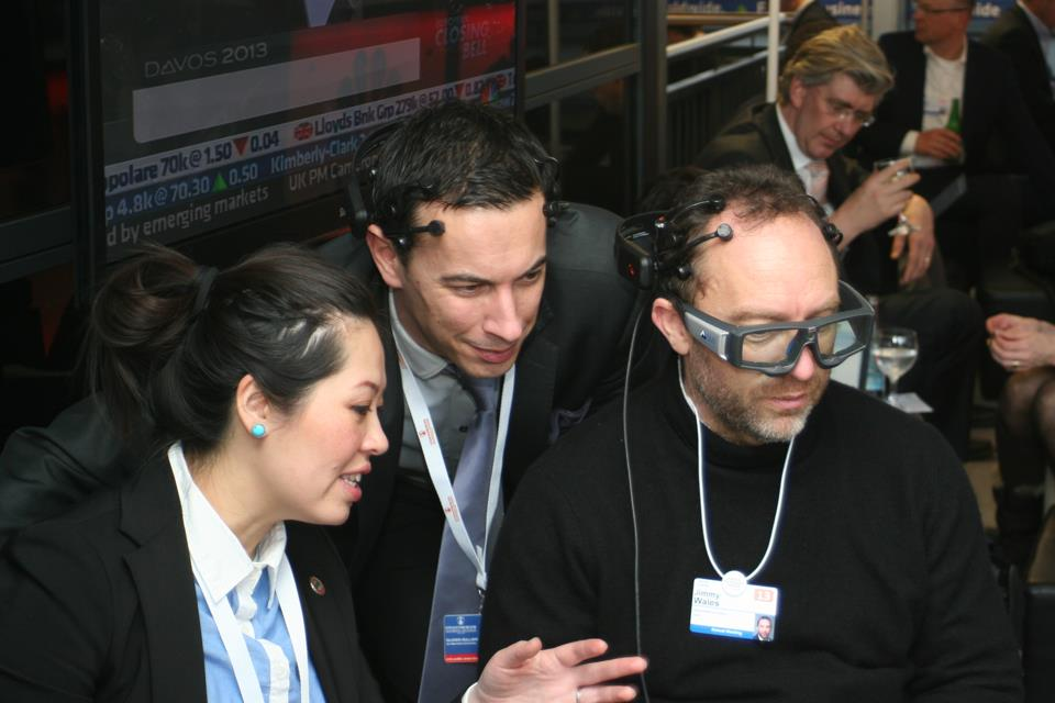 (From left) Emotiv Lifesciences CEO & Founder Tan Le and neuroscientist and behavior change expert Olivier Oullier demonstrate to Wikipedia Founder and CEO Jimmy Wales portable Emotiv EPOC EEG and portable eye-tracking by SMI.