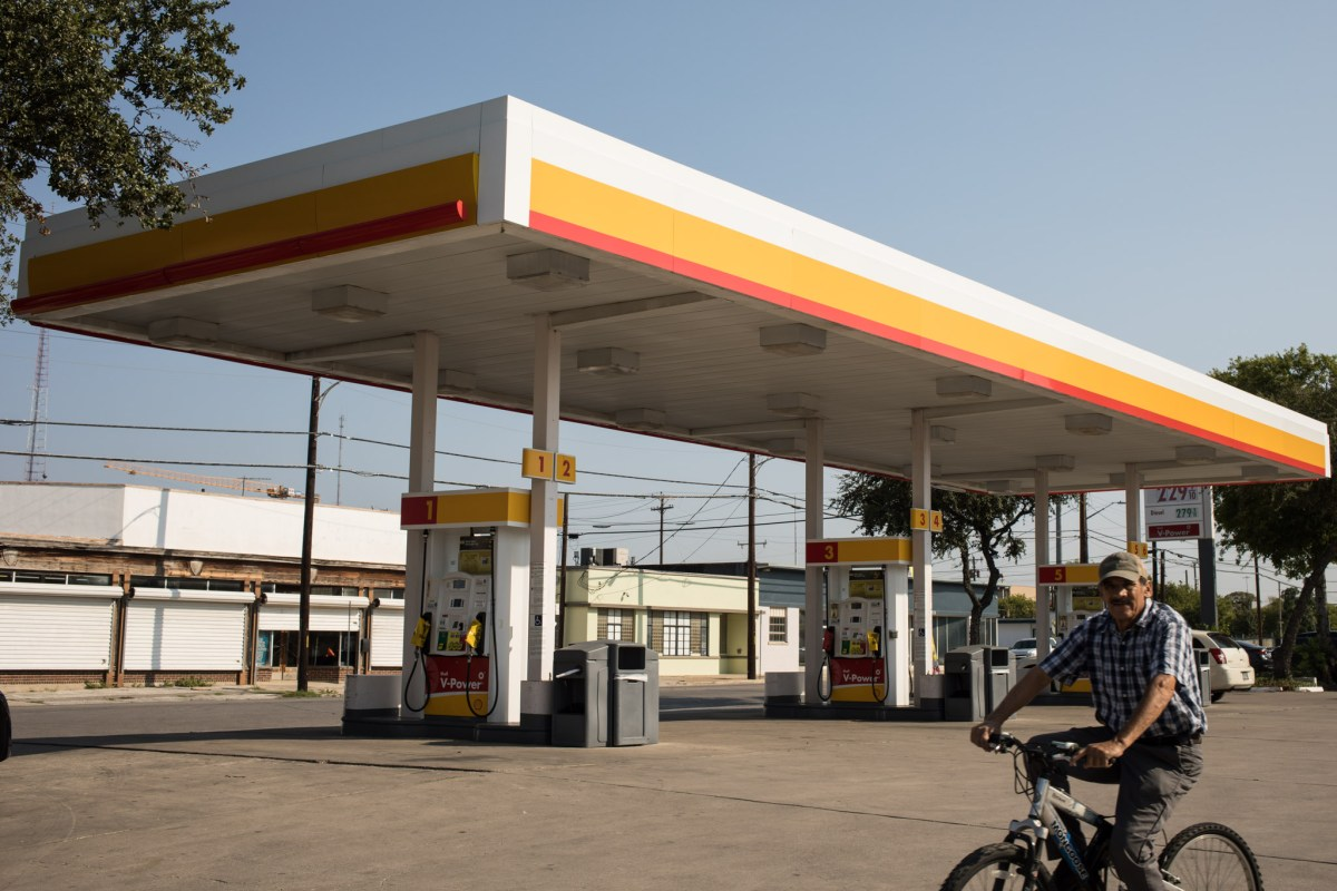 A man rides a bicycle in front of an empty Shell station on the corner of Brooklyn Avenue and Alamo Street. All of the gas station pumps are out of service.