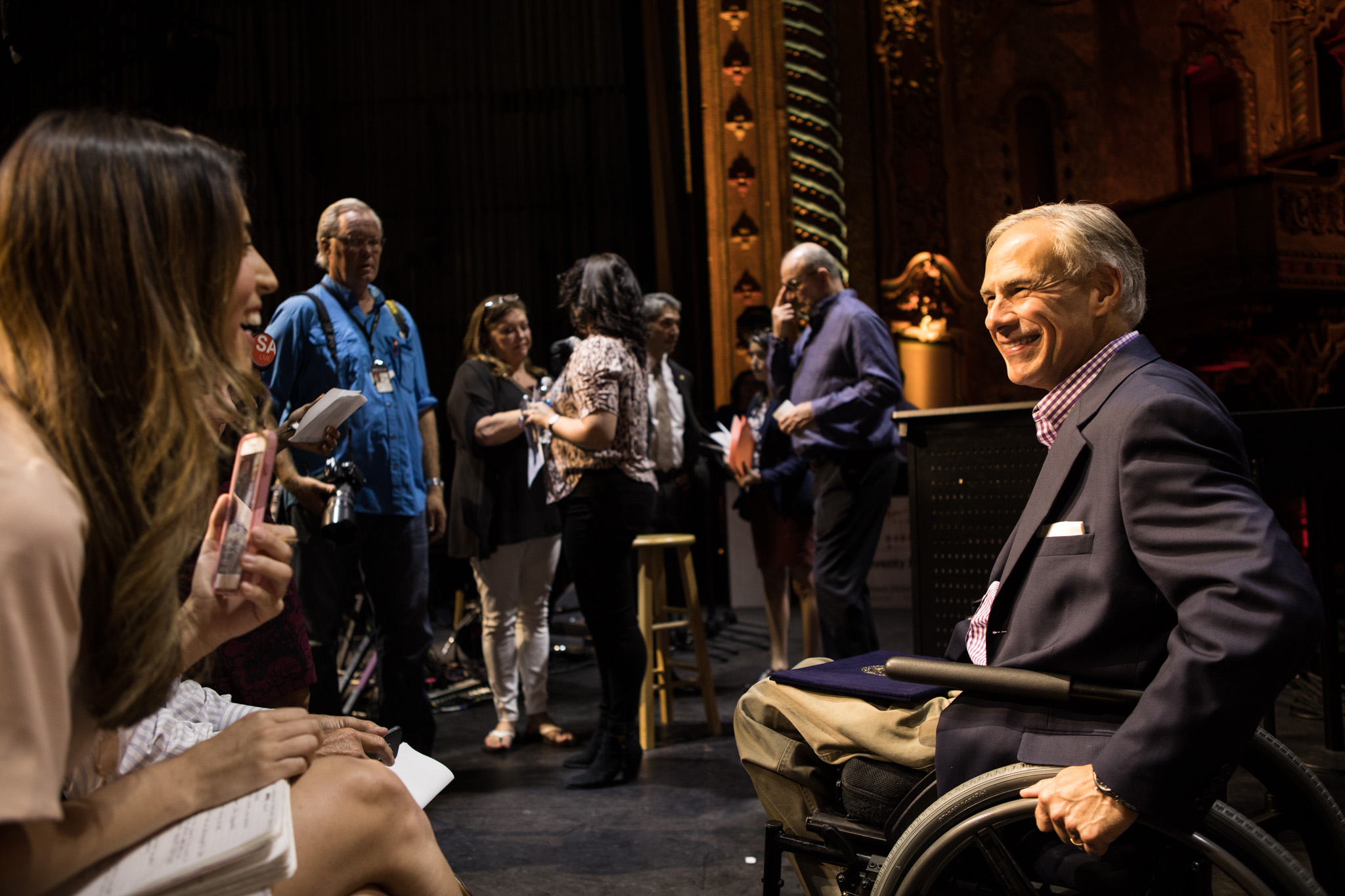 Gov. Greg Abbott greets the media before a press conference at the Majestic Theatre for the George Strait concert.