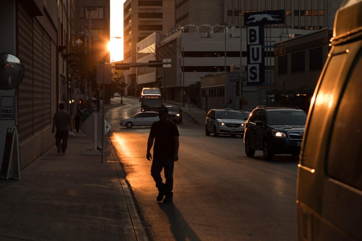 A man walks across Pecan Street downtown before sunset.