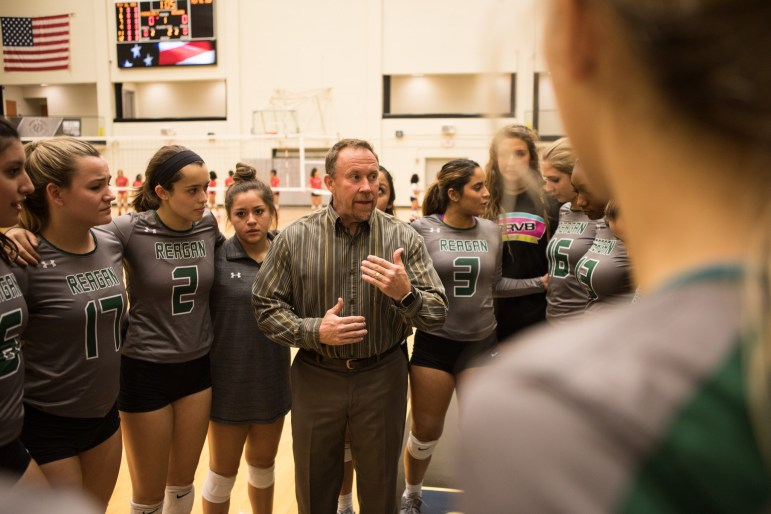 Ronald Reagan High School Volleyball Coach Mike Carter encourages the Reagan Rattlers before their match against Roosevelt High School.