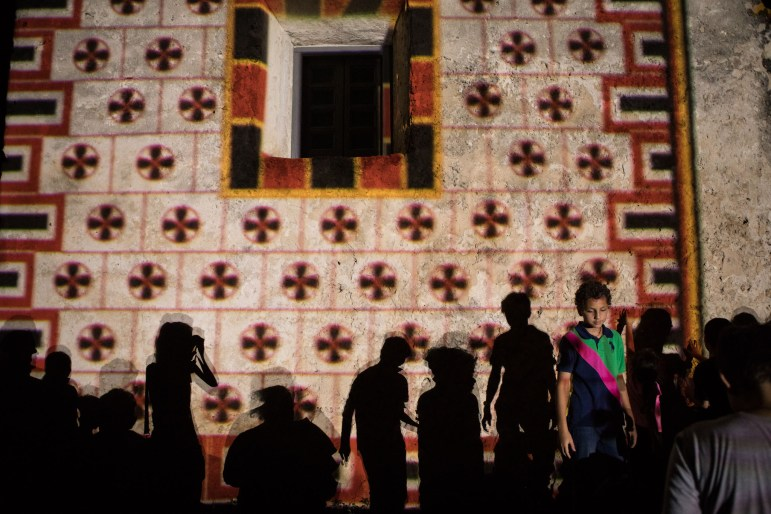 Sebastian, 13, stands along the silhouettes in front of Mission Concepción, lit up to recreate the facade's original designs during Restored By Light.