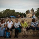 A group of women sit by the sign to Mission Concepción before Restored by Light begins.