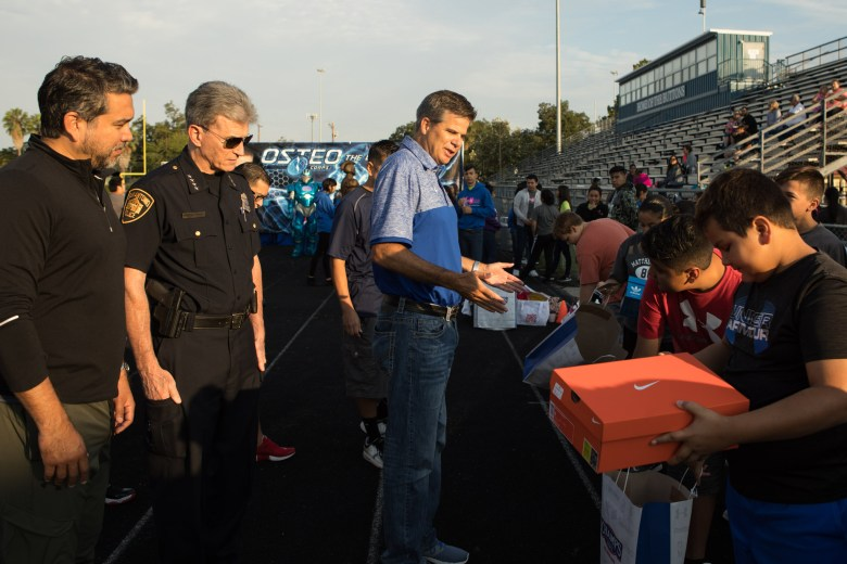 Champs district manager Jim Murto hands out free sneakers to all the participants of the Forward in Fitness program kickoff at Central Catholic High School.