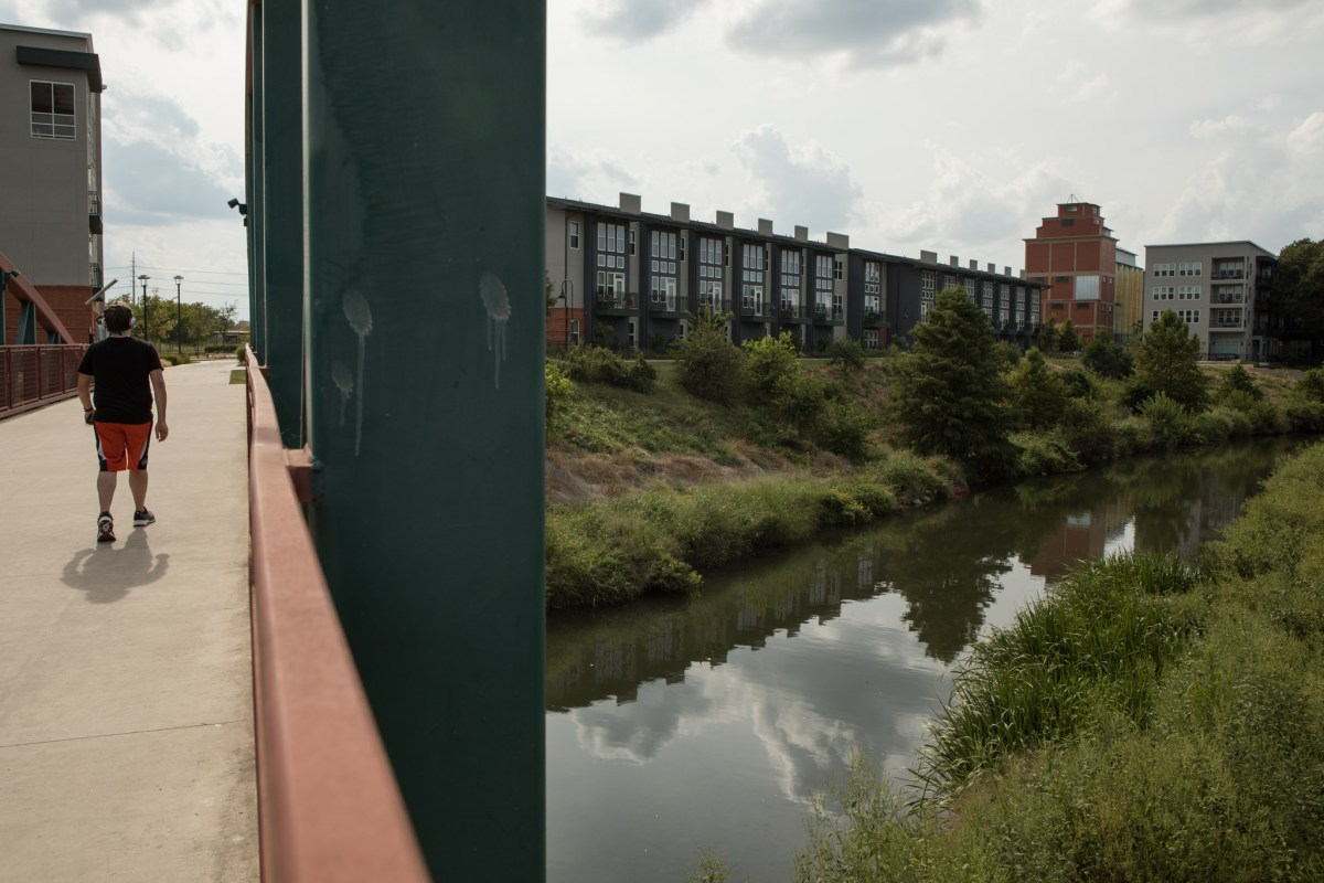 A man walks along a bridge above the San Antonio River in the King William Historic District.
